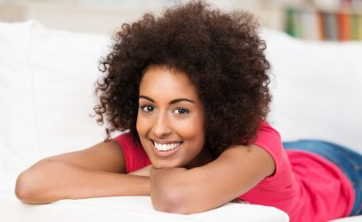 Happy young African American woman with a beautiful smile relaxing on a sofa in her living room smiling at the camera